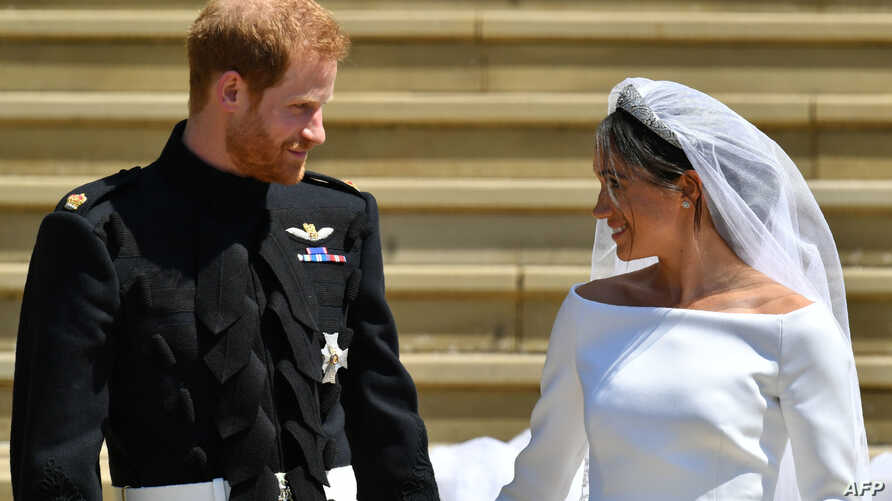 Britain's Prince Harry, Duke of Sussex and his wife Meghan, Duchess of Sussex leave from the West Door of St George's Chapel, Windsor Castle, in Windsor, on May 19, 2018 after their wedding ceremony.