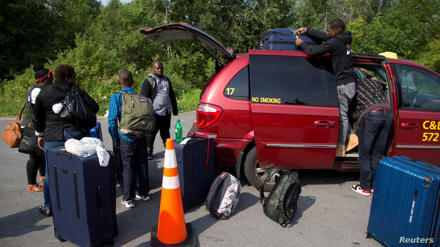 A refugee family claiming to be from Haiti take their luggage from their taxi as they arrive at the U.S.-Canada border on Roxham Road in Champlain, New York, August 3, 2017.