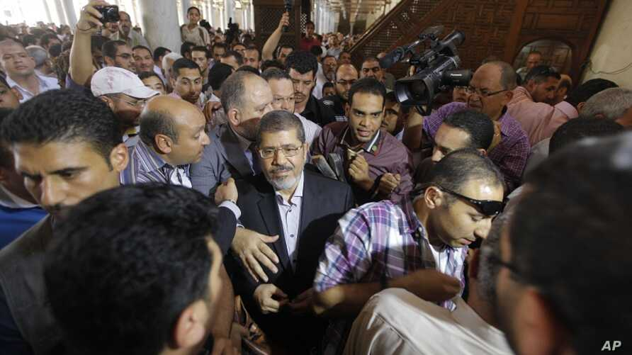 The Muslim Brotherhood's presidential candidate, Mohamed Morsi, center, is surrounded by his supporters after he participated in Friday prayers in Amr Ibn Al-As mosque in Cairo, Egypt, Friday, June 22, 2012.