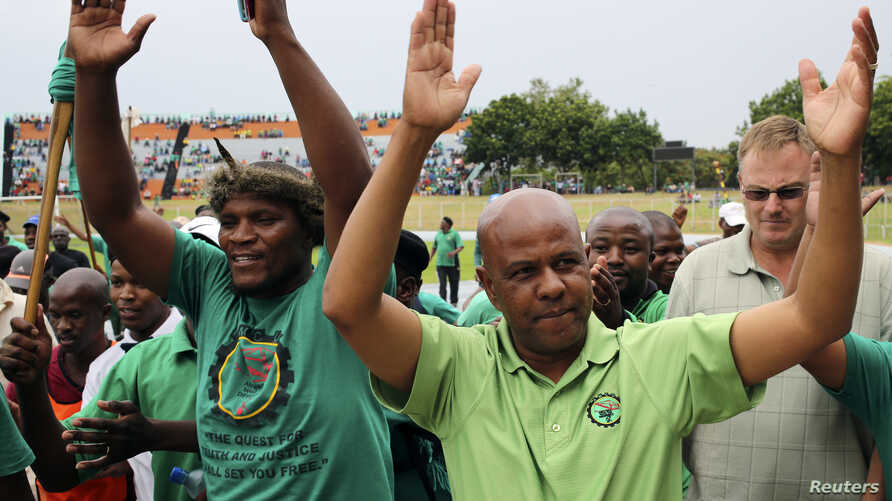 Joseph Mathunjwa (R), president of South Africa's Association of Mineworkers and Construction Union (AMCU), gestures as he arrives to address members of the mining community during a rally in Rustenburg, northwest of Johannesburg Jan.19, 2014.