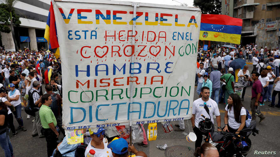 """FILE - Opposition supporters rally against President Nicolas Maduro carrying a sign that reads """"Venezuela is wounded in the heart with hunger, misery, corruption and dictatorship"""", in Caracas, Venezuela, May 10, 2017."""