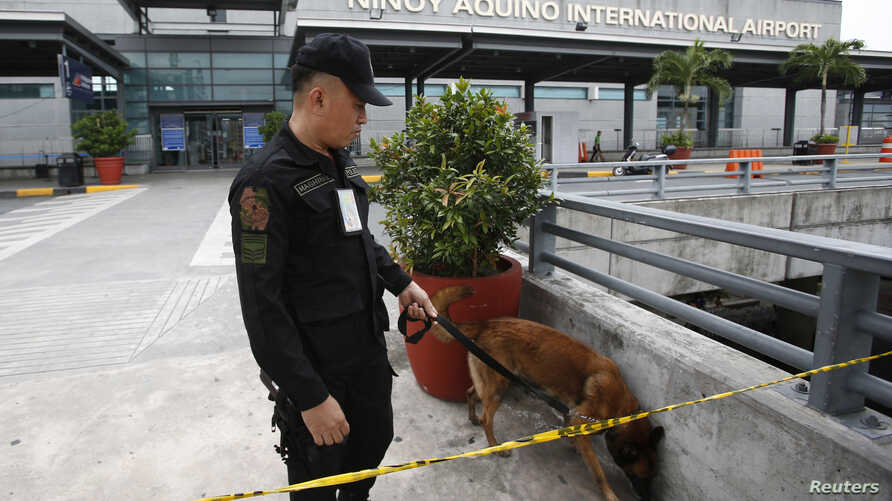 An airport police officer and a sniffer dog patrol Terminal 3 of the Ninoy Aquino International airport in Pasay City, Metro Manila, September 1, 2014.