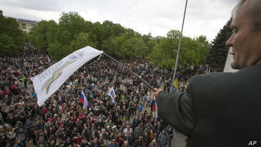 A Pro-Russian activist waves a Donbas Republic flag over a crowd celebrating the capture of an administration building in the center of Luhansk, Ukraine, one of the largest cities in Ukraine's troubled east, Tuesday, April 29, 2014, as demonstrators