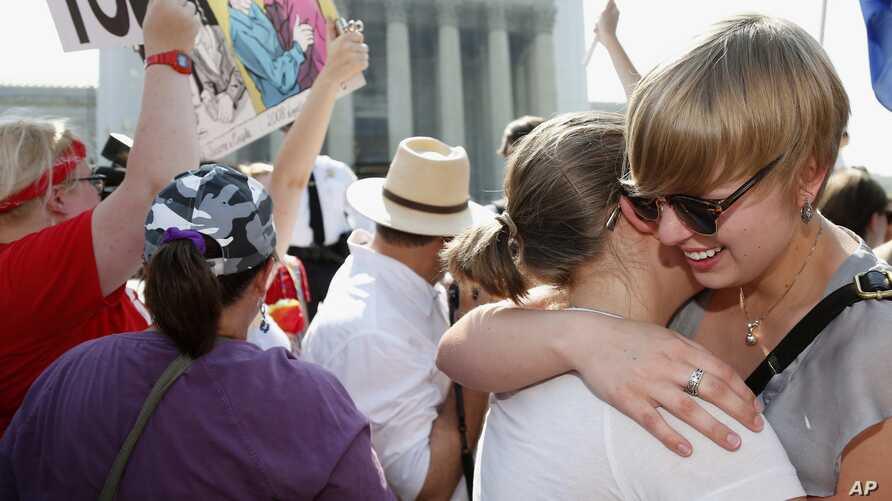 American University students Sharon Burk (L) and Molly Wagner embrace outside the Supreme Court after the court cleared the way for same-sex marriage in California by holding that defenders of California's gay marriage ban did not have the right to a