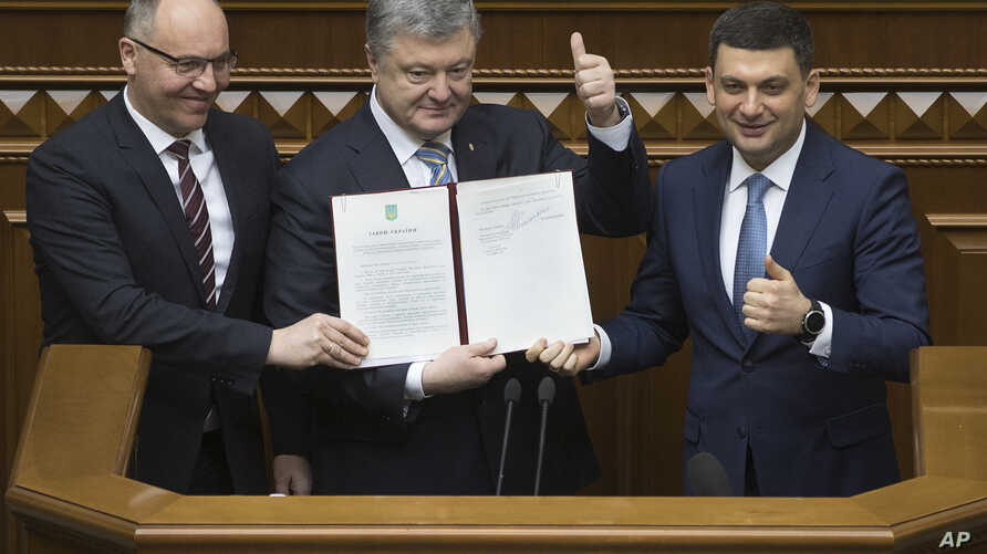 Ukrainian President Petro Poroshenko, center, PM Volodymyr Groysman, right, and parliament speaker Andriy Parubiy are seen with the newly signed Constitutional amendment on pursuing EU and NATO membership, in Kyiv, Feb. 19, 2019.