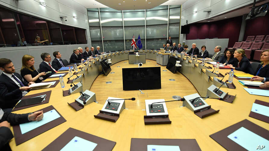 EU Chief Brexit Negotiator Michel Barnier, fifth right, and British Secretary of State David Davis, fourth left, participate in a round table meeting at EU headquarters in Brussels, June 19, 2017.