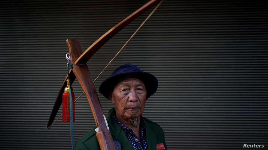 An ethnic Lisu man carries his crossbow as he poses for a photograph during a crossbow shooting competition in Luzhang township of Nujiang Lisu Autonomous Prefecture in Yunnan province, China, March 29, 2018.