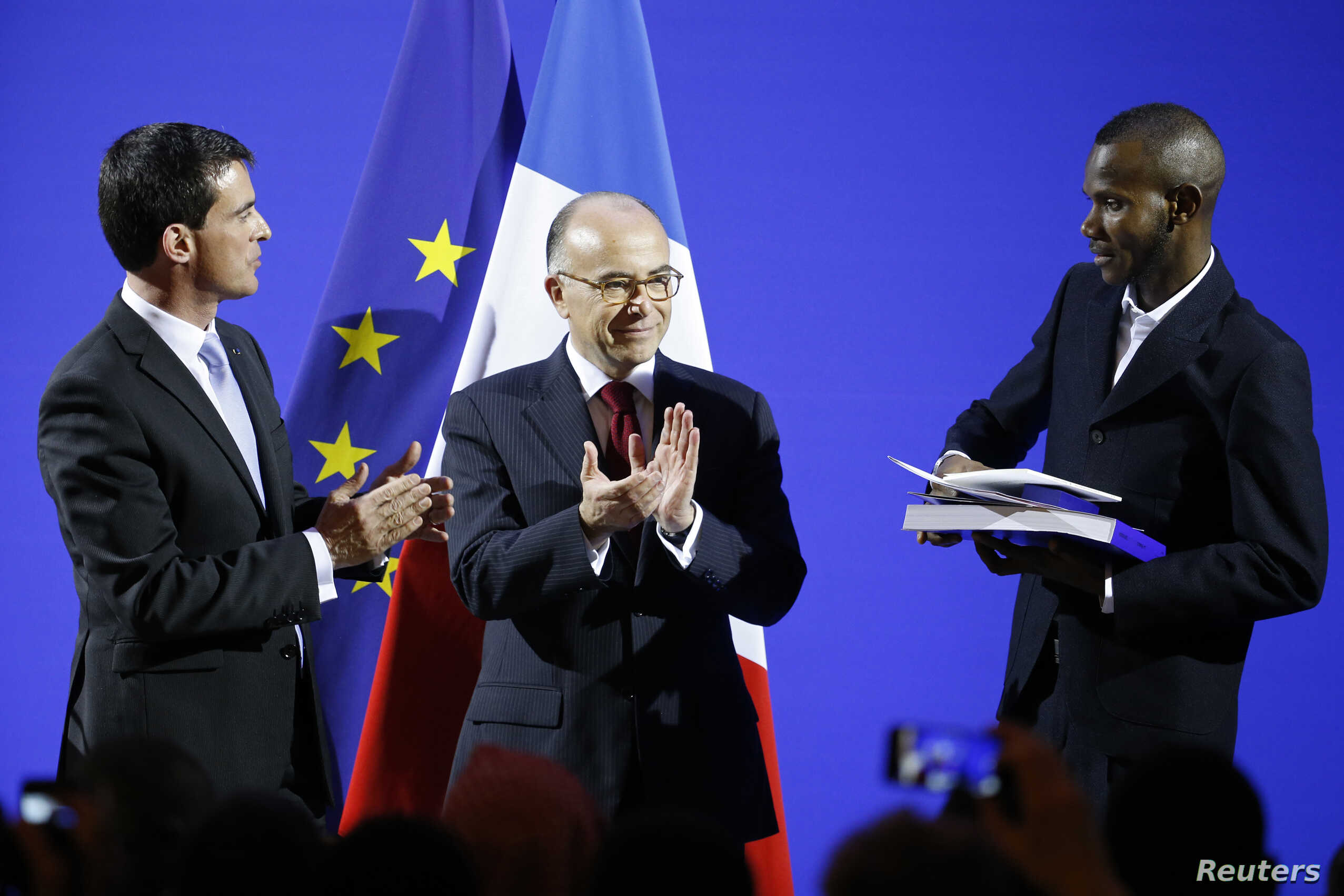 French Prime Minister Manuel Valls and Interior Minister Bernard Cazeneuve applaud as Lassana Bathily, 24, holds his citizenship papers during a ceremony at the Interior Ministry in Paris, Jan. 20, 2015.