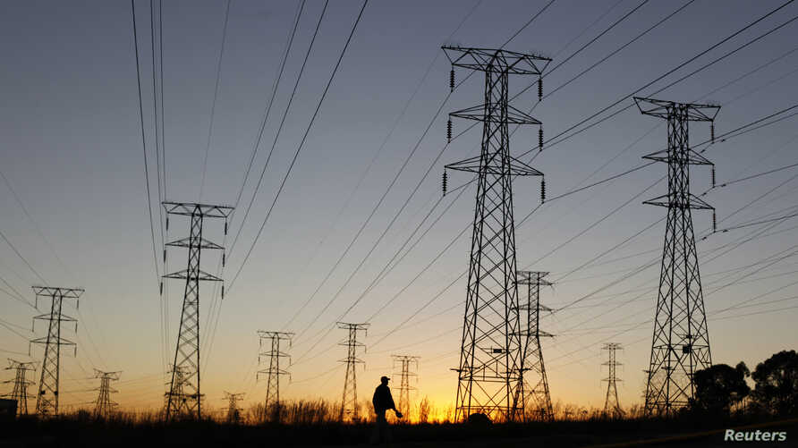FILE - A man walks past electricity pylons as he returns from work in Soweto, outside Johannesburg, May 15, 2012.
