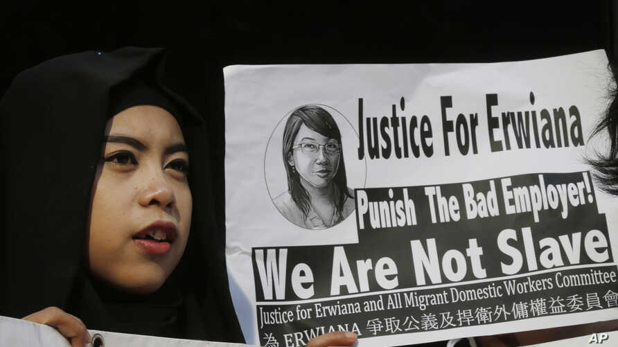 A supporter of Indonesian maid Erwiana Sulistyaningsih, holds a placard as Sulistyaningsih arrives at a court in Hong Kong, Feb. 10, 2015.