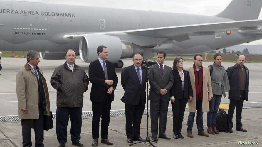 Colombia's government head of negotiators Humberto de la Calle (C) speaks next to delegation members prior to boarding a plane to Oslo, at a military airport in Bogota October 16, 2012. Colombia's government and Marxist rebels will start peace talks