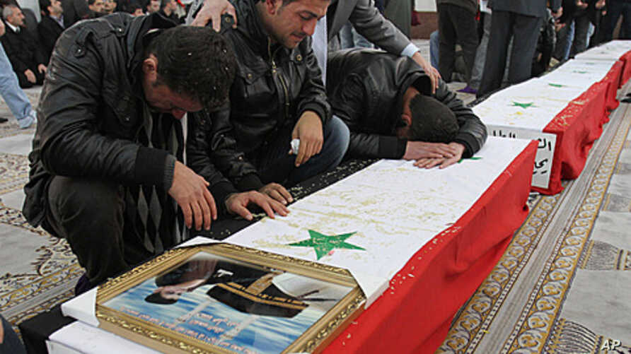 Syrian men mourn over the coffin of one of 11 Syrian police officers who were killed in an explosion in the Midan neighborhood, during a mass funeral procession at Al-Hassan mosque, in Damascus, January 7, 2011.