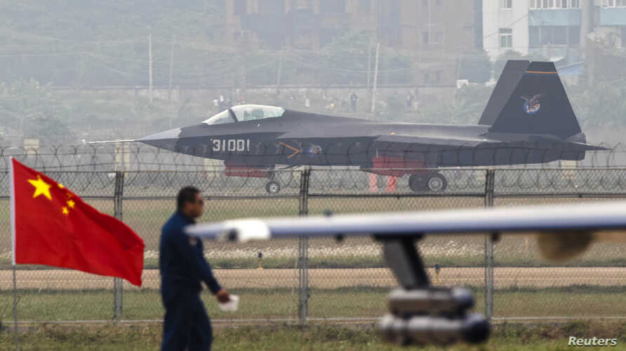 A China-made J-31 stealth fighter (background) lands on a runway after a flying performance at the China International Aviation and Aerospace Exhibition in Zhuhai, Guangdong province, Nov. 11, 2014.