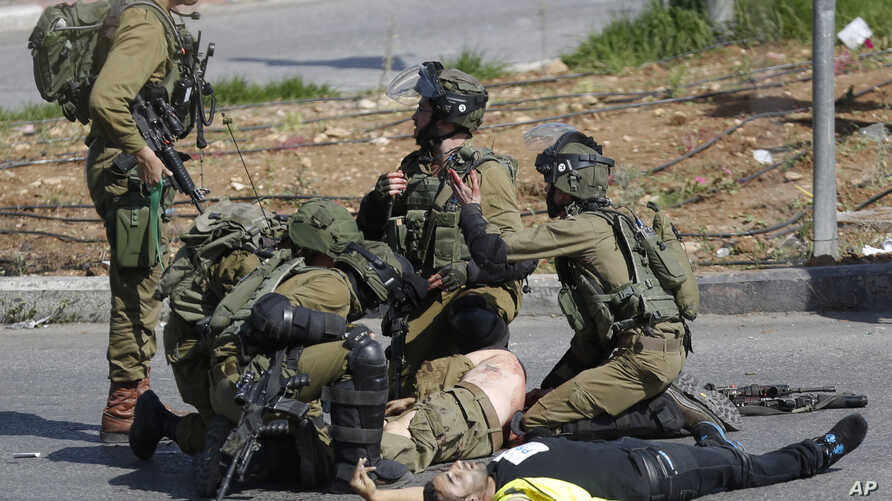 Israeli soldiers treat a wounded comrade after he was stabbed by a Palestinian, wearing a yellow vest, during clashes in the West Bank, Oct. 16, 2015.