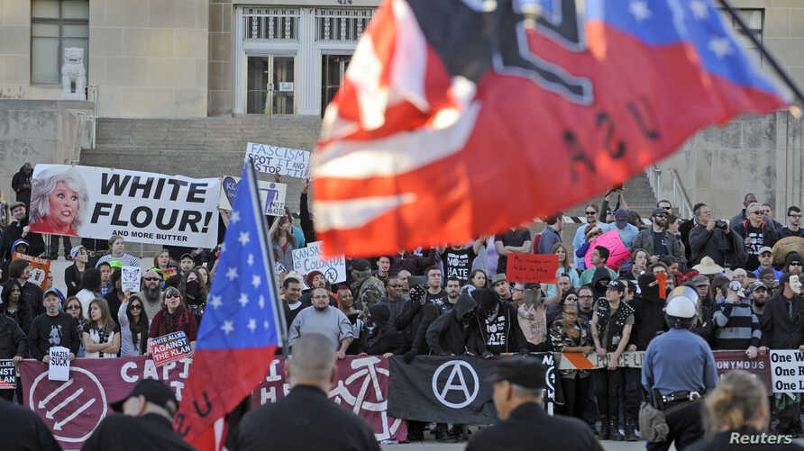 FILE - Counter-protesters yell across the street at city hall during a neo-Nazi rally at the Jackson County Courthouse in Kansas City, Missouri, Nov. 9, 2013.