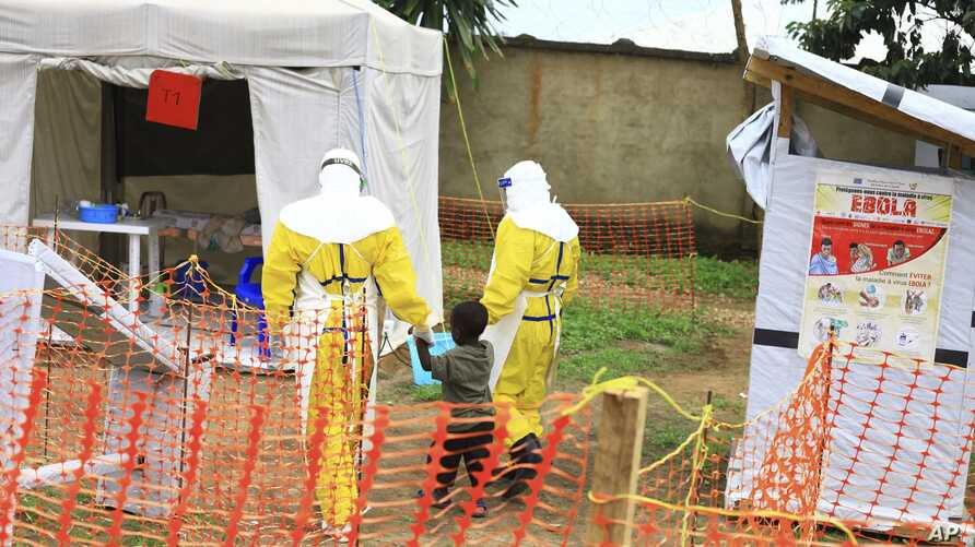 FILE - In this Sunday, Sept 9, 2018 file photo, health workers walk with a boy suspected of having the Ebola virus at an Ebola treatment centre in Beni, Eastern Congo.