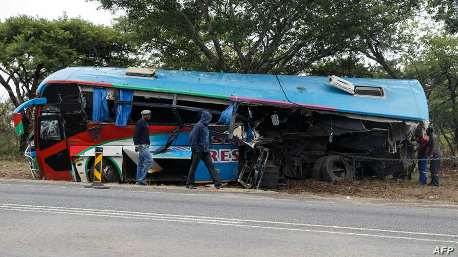People inspect the wreckage of one of two buses that collided Nov. 7, 2018, along the Harare-Mutare highway near Rusape, Zimbabwe, Nov. 8, 2018.
