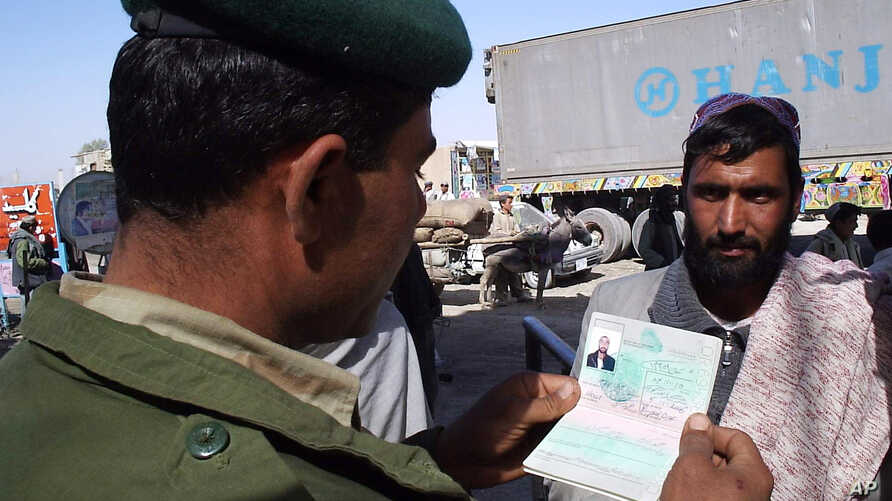 FILE - A Pakistani border guard checks the passport of an Afghan national entering Pakistan through the Chaman post at Pakistan-Afghanistan border.