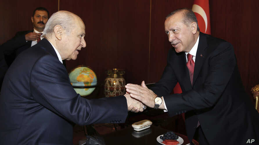 FILE - Turkey's President Recep Tayyip Erdogan, right, shake hands with Devlet Bahceli, the leader of opposition Nationalist Movement Party, at the parliament during its first session in Ankara, Turkey, Oct. 1, 2017.