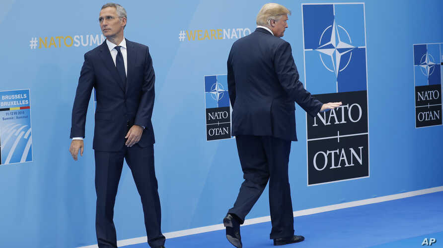 President Donald Trump walks away after being greeted by NATO Secretary General Jens Stoltenberg (L) before a summit of heads of state and government at NATO headquarters in Brussels on July 11, 2018.