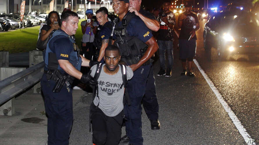 FILE - In this July 9, 2016 photo, police officers arrest activist DeRay McKesson during a protest along Airline Highway, a major road that passes in front of the Baton Rouge Police Department headquarters in Baton Rouge, La., after the fatal shootin
