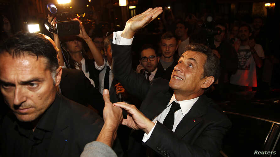 FILE - Former French President Nicolas Sarkozy leaves a restaurant in Paris, July 2, 2014.