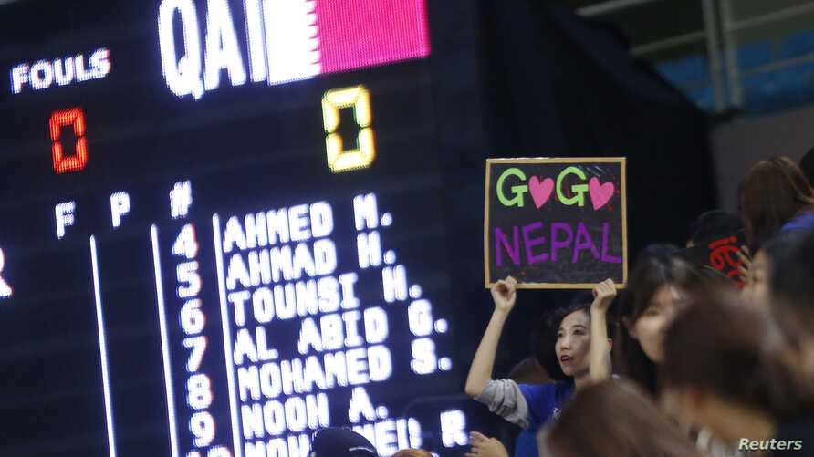 A supporter of Nepal's women's basketball team holds up a sign alongside a scoreboard showing names of Qatar's women's basketball team members after they failed to show up for their scheduled game at the 17th Asian Games in Incheon, South Korea, Sept
