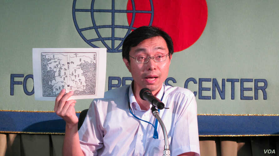 Masaru Sato, Assistant Press Secretary at the Japanese Ministry of Foreign Affairs, holding a 16th-century map of Korea to explain Japan's claim to the island of Takeshima, August 22, 2012. (VOA/Miguel Quintana)