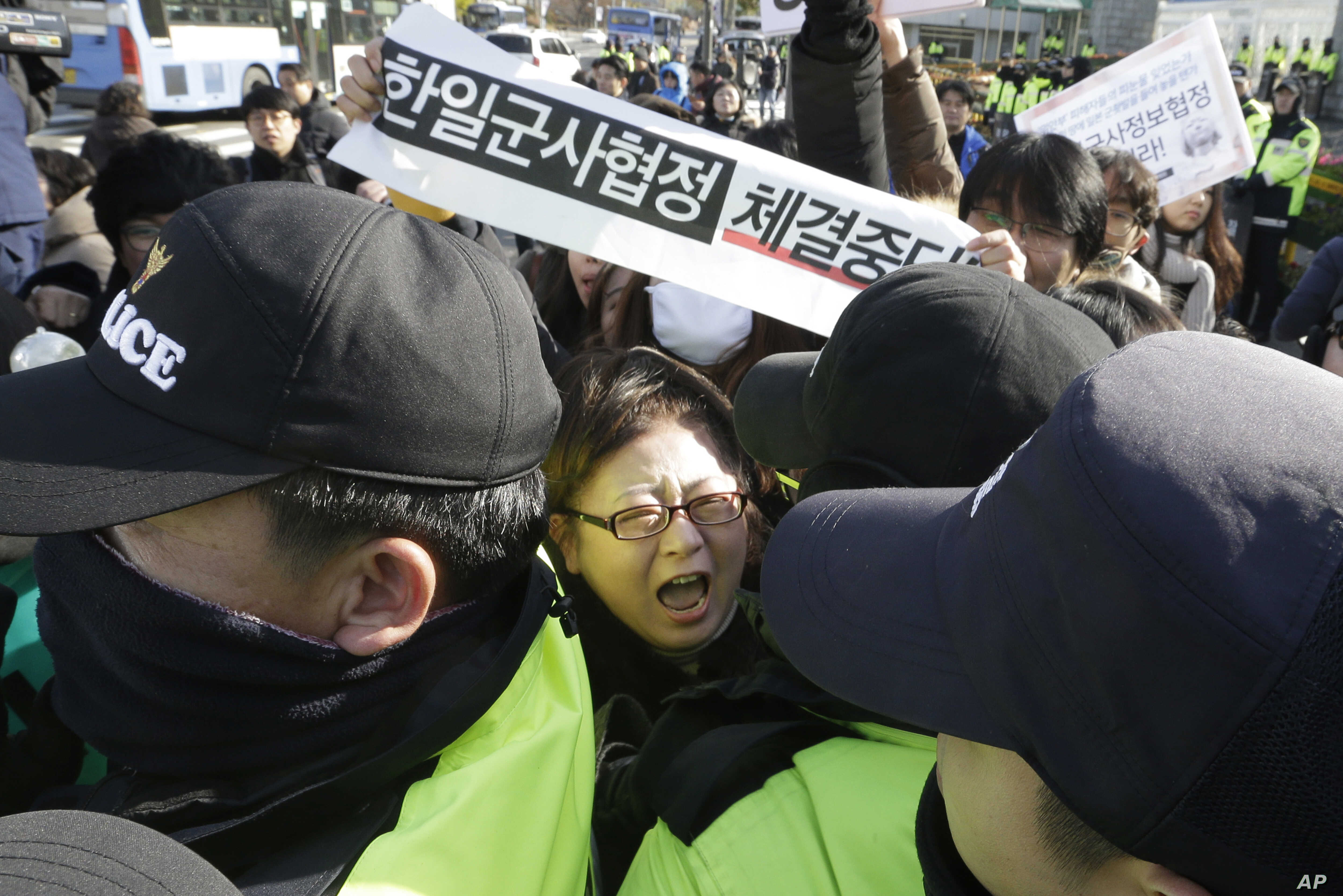 A South Korean protester scuffles with police officers during a rally to oppose the General Security of Military Information Agreement (GSOMIA) between South Korea and Japan, in front of the Defense Ministry in Seoul, South Korea, Nov. 23, 2016.