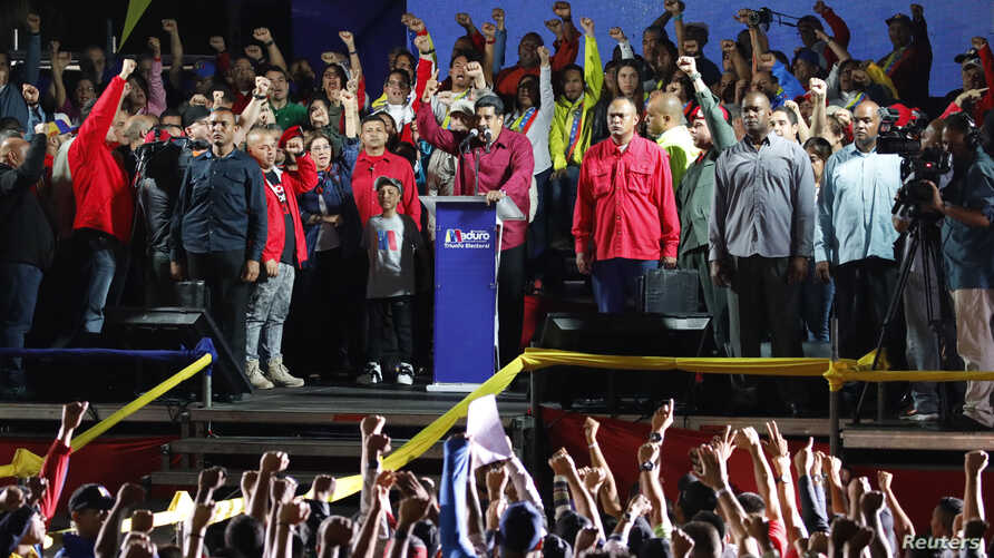Venezuela's President Nicolas Maduro raises a finger as he is surrounded by supporters while speaking during a gathering after the results of the election were released, outside of the Miraflores Palace in Caracas, Venezuela, May 20, 2018.