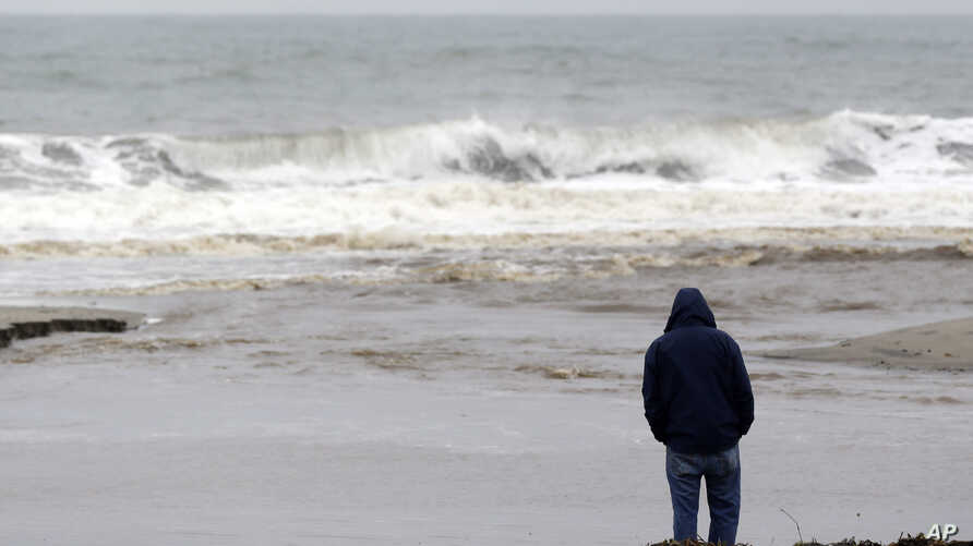 FILE - A man watches ocean waves crash at Seacliff State Beach in Aptos, California.