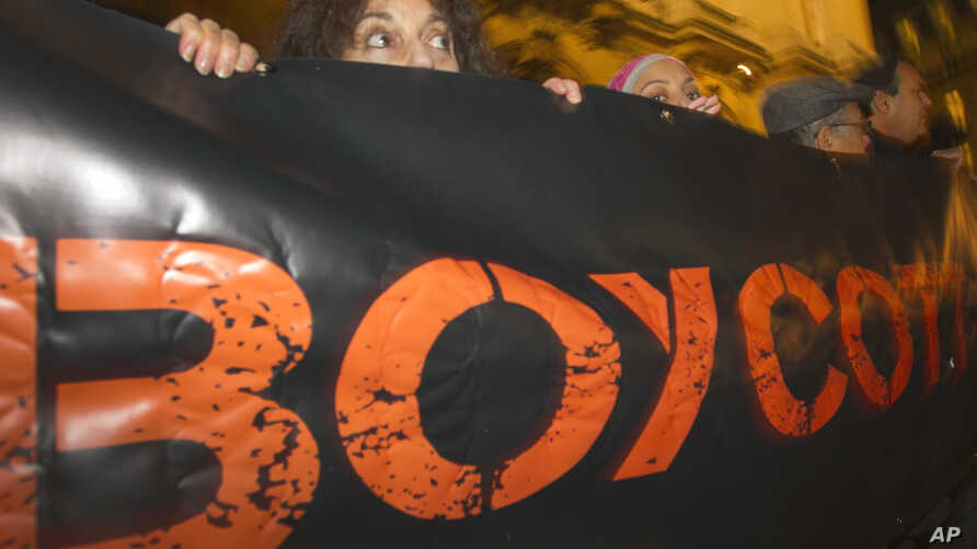 """FILE - In this Oct. 31, 2012, French demonstrators and supporters of Palestinians hold a placard with the word """"Boycott"""" during a demonstration in Paris."""