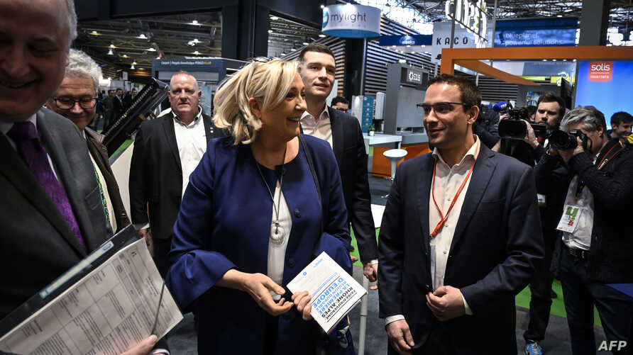 "President of the far-right Rassemblement National (RN) party and French MP Marine Le Pen (C) and French far-right 'RN' runner candidate for the upcoming European election Jordan Bardella (C-R) visit the annual energy transition fair ""BePOSITIVE"" exhi"
