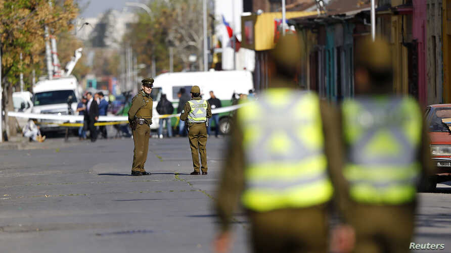 Police officers stand guard at an area where a bomb exploded in Santiago, Chile, Sept. 25, 2014.