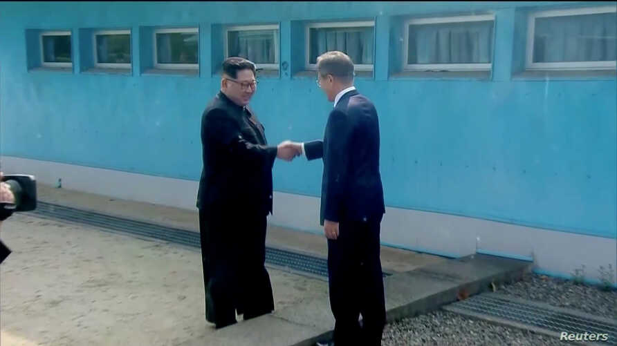 North Korean leader Kim Jong Un shakes hands with South Korean President Moon Jae-in at the concrete border as both of them arrive for the inter-Korean summit at the truce village of Panmunjom, in this still frame taken from video, South Korea April ...