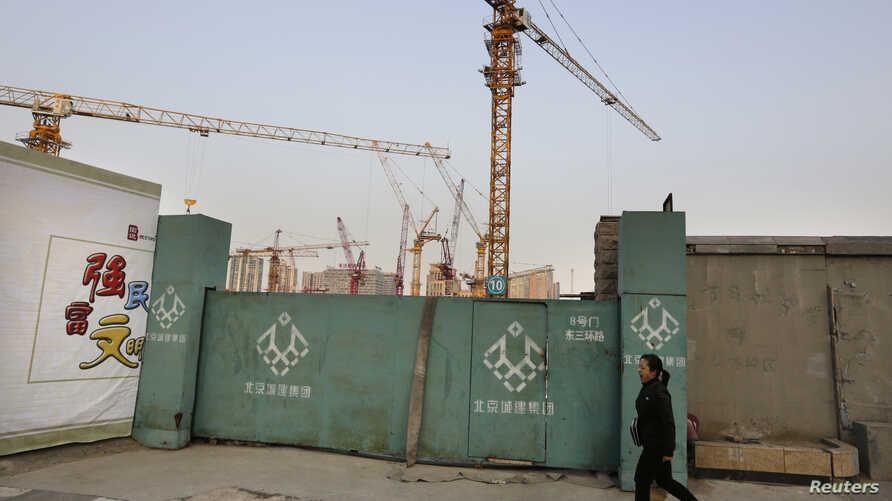 A woman walks along a construction site in Beijing's central business district, Oct. 21, 2014.