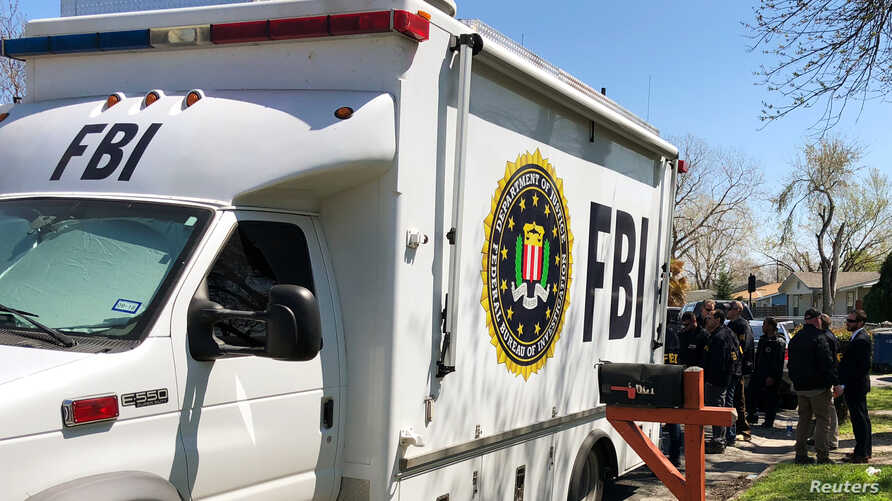 Law enforcement personnel including FBI agents are seen March 13, 2018, near a home that was hit with a parcel bomb in Austin, Texas.