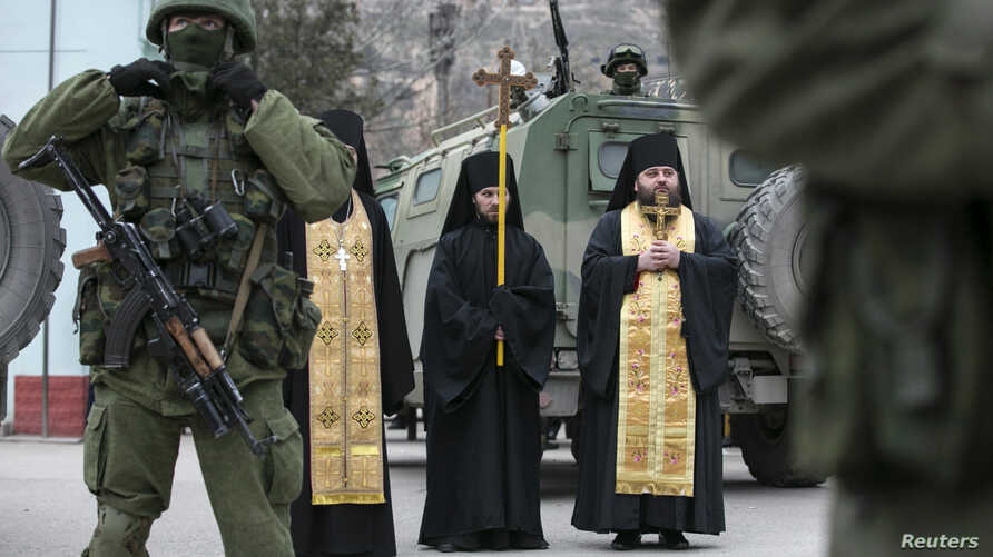 Orthodox monks pray next to armed servicemen near Russian army vehicles outside a Ukrainian border guard post in the Crimean town of Balaclava March 1, 2014. Russian President Vladimir Putinsecured his parliament's authority on Saturday to invade Ukr