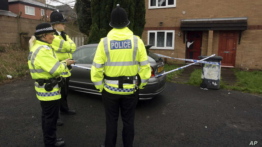 FILE - Police officers stand guard outside a property during a raid in Manchester, England.
