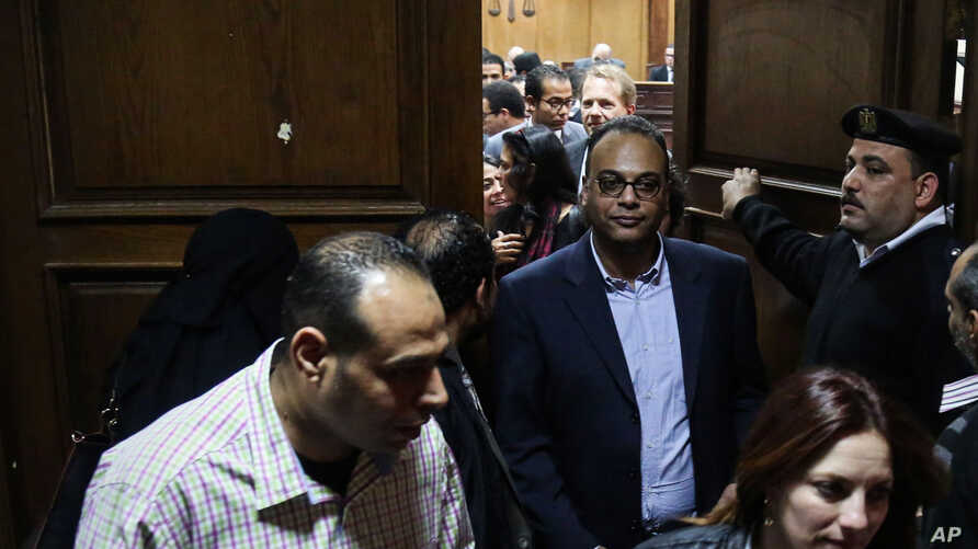 Investigative journalist Hossam Baghat, center, leaves a courtroom at the Cairo Criminal Court after the court postponed a decision on whether to implement an order to freeze his assets over allegations of illegal foreign funding, in Cairo, Egypt, Ma