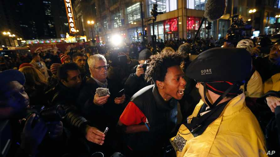 "Lamon Reccord, second from right, yells at a Chicago police officer ""Shoot me 16 times"" as he and others march through Chicago's Loop Wednesday, Nov. 25, 2015."