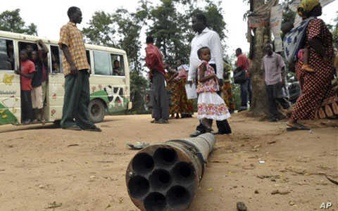 People walk past munitions laying in the street at Pugu-Majohe on the outskirt of Dar es Salaam, following several explosion that occurred at a military base, February 17, 2011