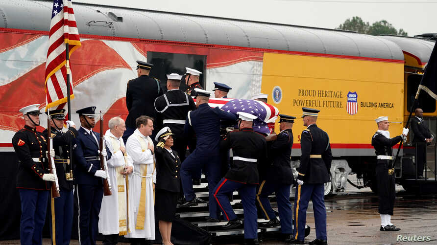 The flag-draped casket of former President George H.W. Bush is carried by a joint services military honor guard, Dec. 6, 2018, in Spring, Texas, as it is placed on a Union Pacific train.
