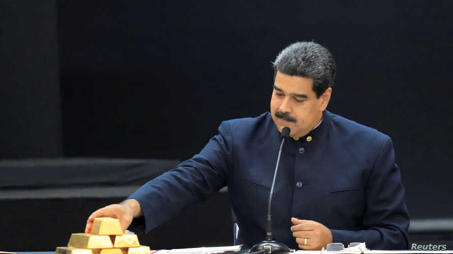 FILE - Venezuela's President Nicolas Maduro touches a gold bar as he speaks during a meeting with the ministers responsible for the economic sector at Miraflores Palace in Caracas, Venezuela, March 22, 2018.
