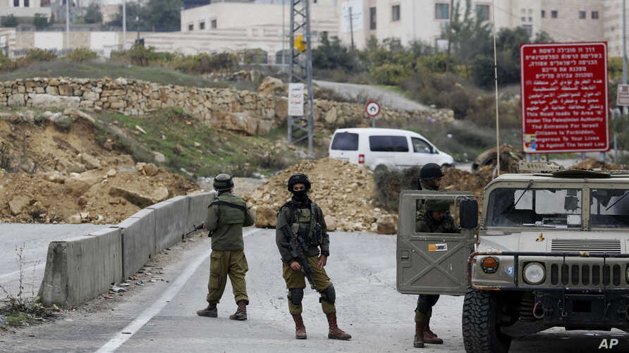 FILE - Israeli soldiers stand guard after the military blocked the road with an earth berm at one of the exits of the West Bank city of Hebron, Nov. 7, 2015.