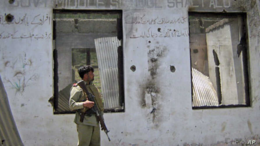 A soldier stands guard at the site of clashes between militants and security forces in Upper Dir, along Pakistan's border with Afghanistan, June 3, 2011