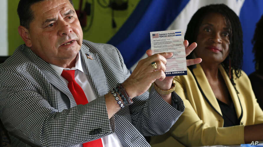 FILE - Francisco Portillo, left, president of the Honduran organization Francisco Morazan, holds up a postcard addressed to President Donald Trump asking him to extend Temporary Protected Status for tens of thousands of Central Americans and Haitians