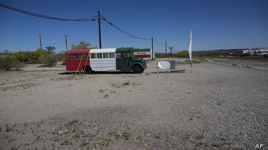 """FILE - A bus painted in a Mexican flag motif and a banner with the Spanish farewell for """"have a nice trip,"""" serves as a roadside advertisement for a Chevron station, in Ajo, Arizona, April 4, 2017. In the past month, three large groups of migrants ha"""