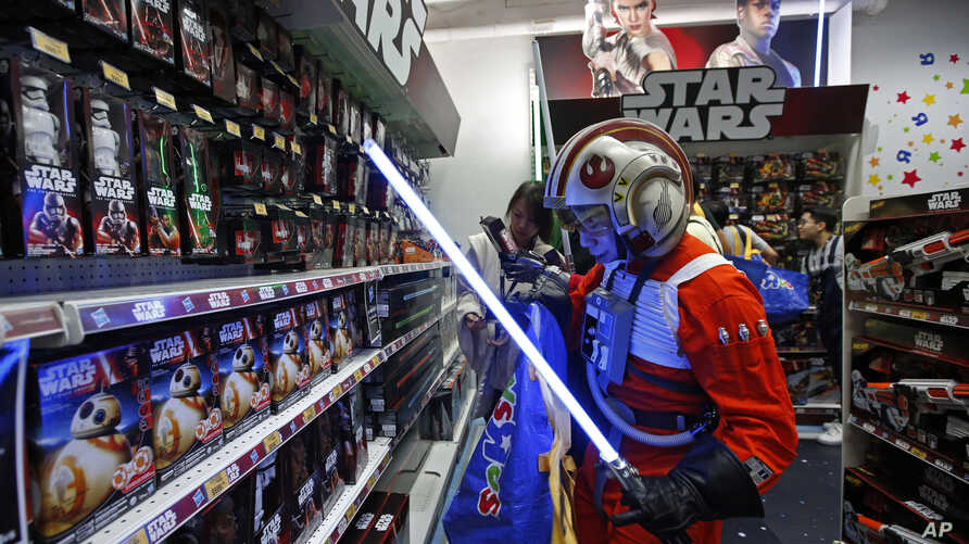 """A fan dressed as a Star Wars character shops at a toy store at the midnight in Hong Kong, Sept. 4, 2015, as part of the global event called """"Force Friday"""" to release new toys and other merchandise of the new movie """"Star Wars: The Force Awakens."""""""