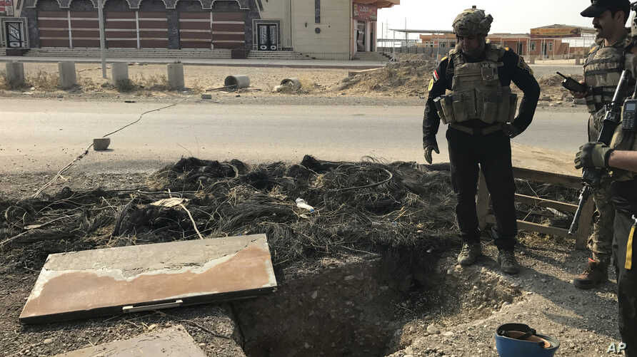 A soldier with Iraq's elite counterterrorism force inspects a tunnel made by Islamic State militants in Bartella, Iraq, Oct. 27, 2016. The town of Bartella in northern Iraq is about 20 kilometers east of Mosul.